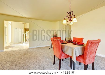 Spacious Creamy Tones Interior Of Dining Room With Red Chairs.