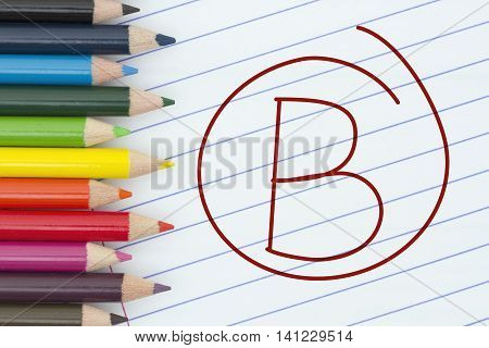 Being a B grade student Pencil Crayons with loose leaf paper and a grade B