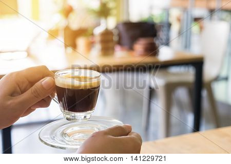 Woman hand holding hot espresso shot at coffee shop.