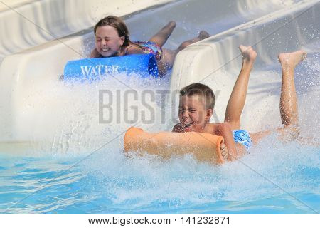 Rhodes Greece-August 1, 2016:Girl and boy on the mat racer slide.Mat racer slide is very popular for young people in the Water Park. Water Park is located on the island of Rhodes in Greece and one of the most largest in Europe and is a very popular place
