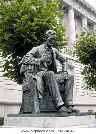 Side angle of Statue of Abe Lincoln sitting down looking downwards in Front of City Hall in San Francisco poster