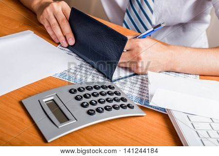 Close-up of a Businessman Writing a Check on Desk