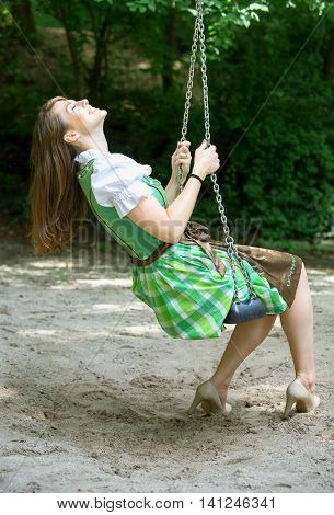 bavarian woman in dirndl sitting on swing at a playground