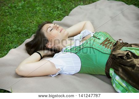 young bavarian woman in dirndl lying on blanket in grass