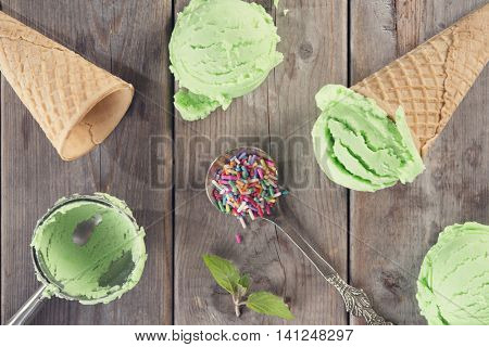 Top view green ice cream in a waffle cones with color rice and utensil over old rustic wooden background.
