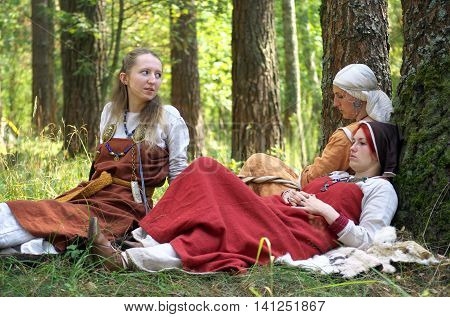 Smolensk, Russia - August 09, 2014 Girls in old Russian national dress sitting in the woods on a halt at the festival of historical reconstruction