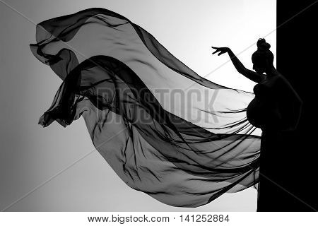 Beautiful woman face close up studio on black and white background with flowing fabric