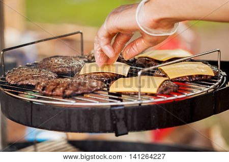 Closeup of a man's hand, spread the cheese on the burger patties on the barbecue-party