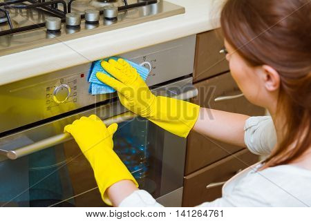 Cleaning the oven concept. Woman in gloves and an apron in the kitchen washing the oven door