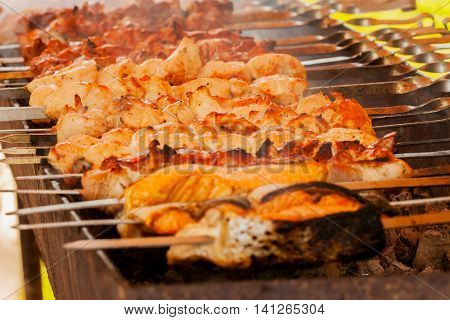 Different types of delicious meat and fish on skewers grilling during the summer picnic outdoors