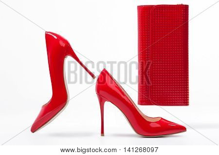 isolated red stylish stiletto shoes with clutch bag; studio shot of classic woman footwear and accessories;