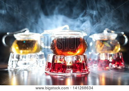 Three Glass Teapots With Candle Heaters And Backlighted Smoke On Background;
