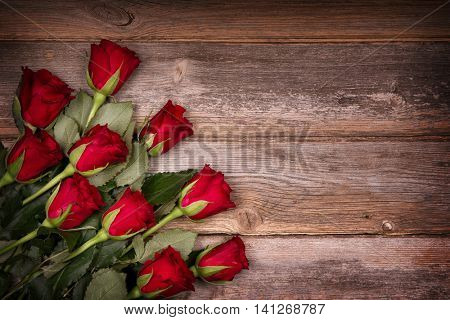 Red roses over old wood background with intentional vignette. Ideal image for Birthday, Valentine and celebration cards.