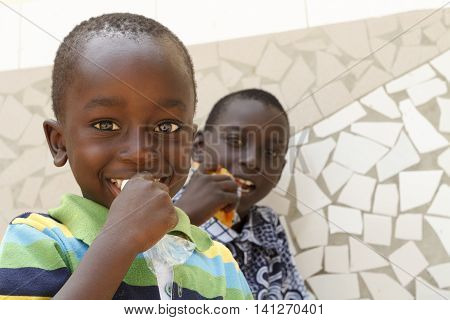 SENEGAL AFRICA - APRIL 24 2016: Two unidentified bright-eyed Senegalese kids eating snacks during a visit to their village.