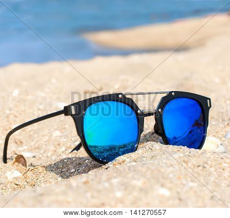 blue mirrored sunglasses on the sand overlooking the sea the concept of summer beach holidays