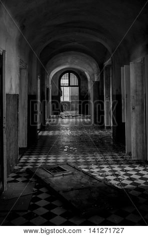 Abstract image of a dark spooky corridor in an old abandoned hospital building with shatter on the checkered floor
