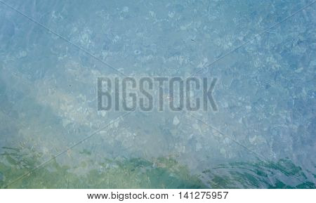 Transparent water of sea ocean and pebbles on the bottom. Sea water background. Sea bottom with pebbles underwater. Clear water background blue aqua natural texture. Copy space.