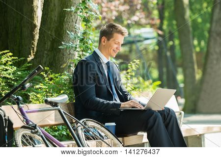 Happy Male Businessman Sitting On Bench Using Laptop At Park