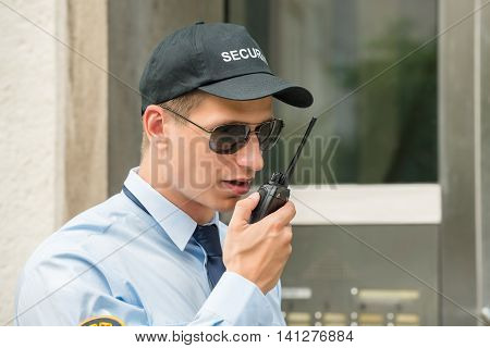 Close-up Of Male Security Guard Talking On Walkie-talkie