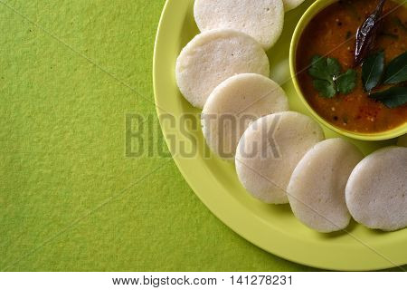 Idli With Sambar In Bowl On Green Background, Indian Dish : South Indian Favourite Food Rava Idli Or