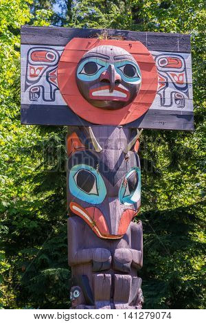 Vancouver Canada - July 24 2016: One of nine totem poles at Hallelujah point in Stanley Park. The top shows two masks in maroon and purple. Green trees as background.