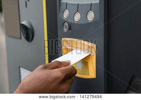 Close-up Of Person's Hand Inserting Ticket Into Parking Machine To Pay For Parking