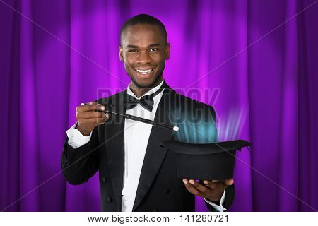 Young Happy Magician Showing Magic With Magic Wand And Hat