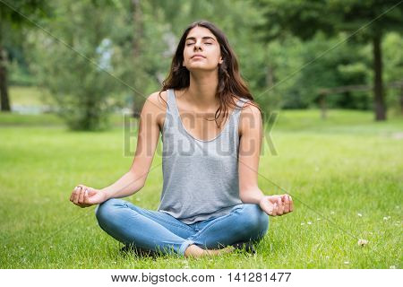 Young Woman Sitting On Green Grass Doing Meditation In Park