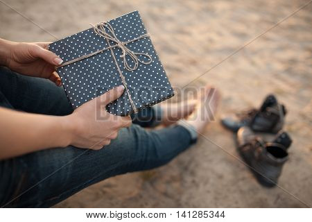 female makes notes and sitting on the beach; woman writes in diary and sitting on sand;