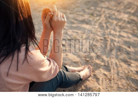 barefoot female sitting on sand in rays of sun; bootless woman on beach at sunset;