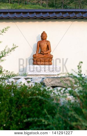 Buddha statue among the green branches in a garden of stones in the territory of a Buddhist temple. Datsan Rinpoche Bagsha on Bald Mountain in Ulan-Ude, Buryatia, Russia.