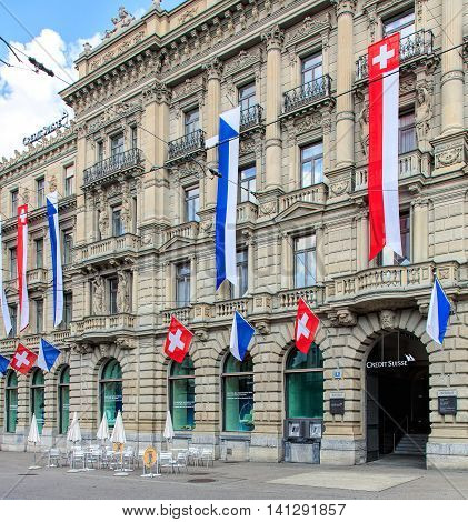 Zurich, Switzerland - 30 July, 2016: facade of the Credit Suisse building on Paradeplatz square decorated with flags of Switzerland and Zurich. Credit Suisse Group is a Swiss multinational financial services holding company.