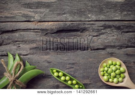 Green peas in wooden spoon on old wooden background