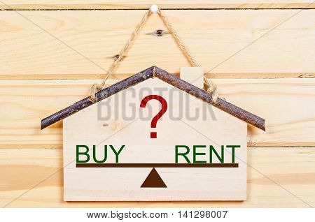 Concept of choice between buy or rent with wooden home model.