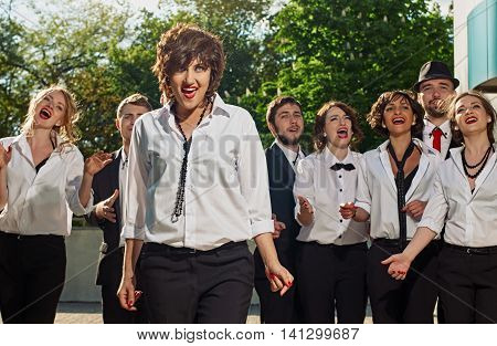 singing cheerful friends dressed tuxedo in the summer city. green trees are background. they are vocals group with leader.