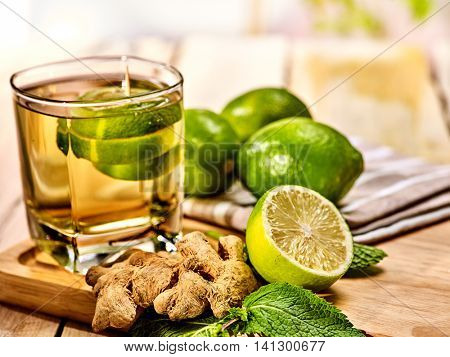 Healthy detox drink with ginger . On wooden boards glass with green tea and mint. Mint ginger drink number three hundred thirty five with half lime .