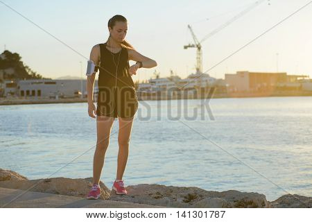 Young Sporty Girl Watching At Her Watch On The Beach