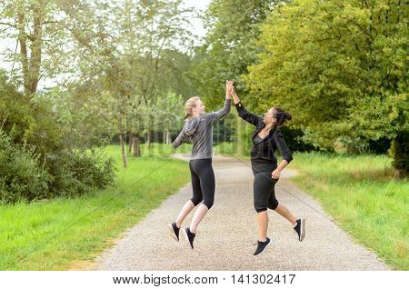 Happy Jumping Women Congratulating Each Other