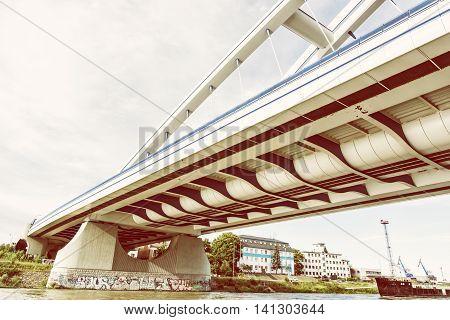 Modern Apollo bridge in Bratislava Slovak republic. Yellow photo filter. Architectural theme. Ship transportation. Infrastructure theme. Danube river.