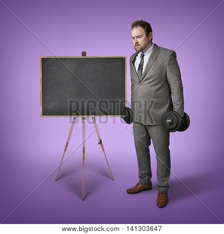 Businessman with wieghts and blackboard at office