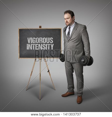 Vigorous intensity muscleman text on blackboard with businesssman holding weights