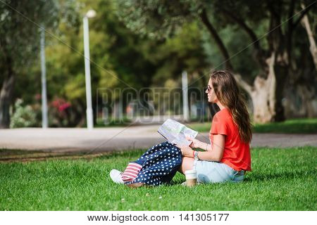 Happy Female Tourist Relaxing In Park