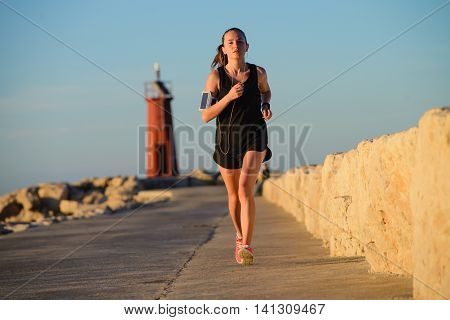 Young Sporty Girl Running Alone At Beautiful Sunset Near The Lighthouse.