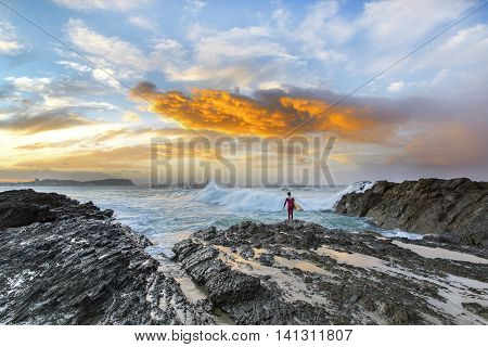 Surfer contemplating the ocean waves during sunset at Currumbin Rock, Gold Coast
