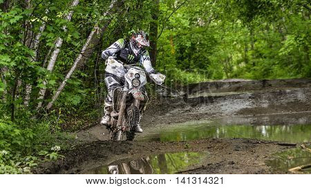 Khabarovsk, Russia - may 30. 2016 : unknown rider in action on stage Enduro Khabarovsk . Motorcyclists ride in the mud with a big splash