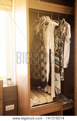 Clothes hang on a shelf in a designer clothes store, Modern closet with row of clothes hanging in wardrobe, Vintage rooms and personal belongings kept in the room which feeling luxury and relax.