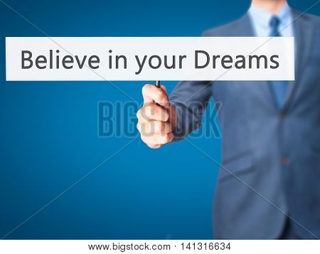 Believe In Your Dreams - Businessman Hand Holding Sign