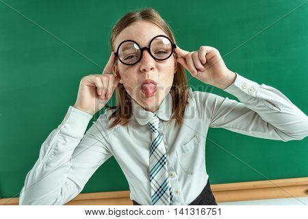 Naughty pupil making sassy funny expressions showing her tongue / photo of teen school girl wearing glasses creative concept with Back to school theme