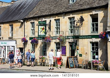 BURFORD, UNITED KINGDOM - JULY 20, 2016 - View of The Golden Pheasant Inn along The Hill shopping street with tourists passing by Burford Oxfordshire England UK Western Europe, July 20, 2016.