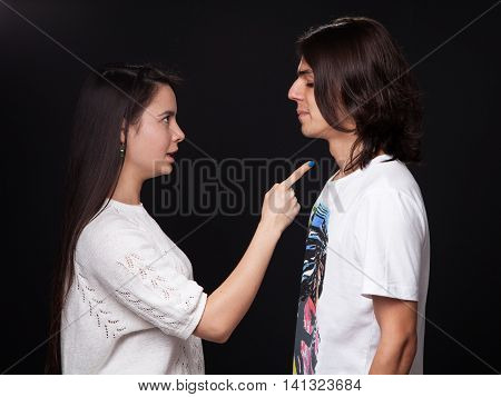 Family quarrel - woman is wagging her finger threatening the man black background
